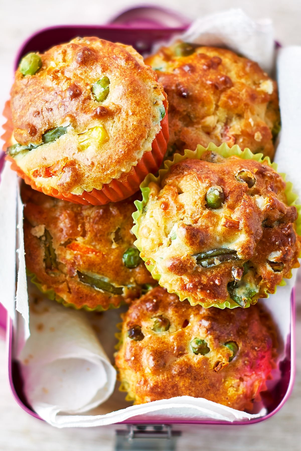 Savoury vegetable muffins in a pink lunchbox lined with paper. The muffins have golden brown tops, studded with peas and beans.