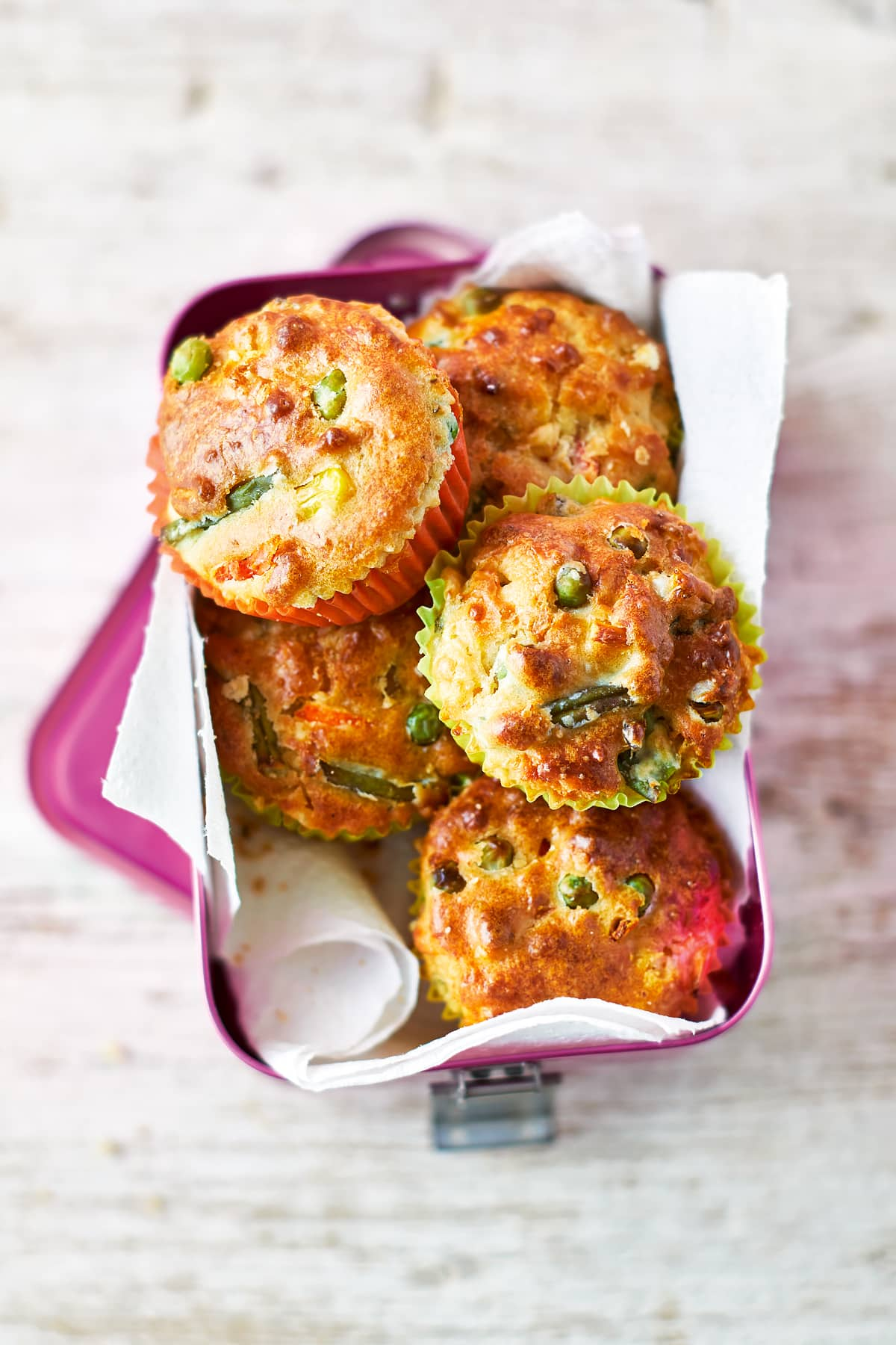 Savoury vegetable muffins in a pink lunchbox lined with paper on a wooden background. The muffins are in multicoloured cases and the tops are studded with carrots, peas, beans and sweetcorn.