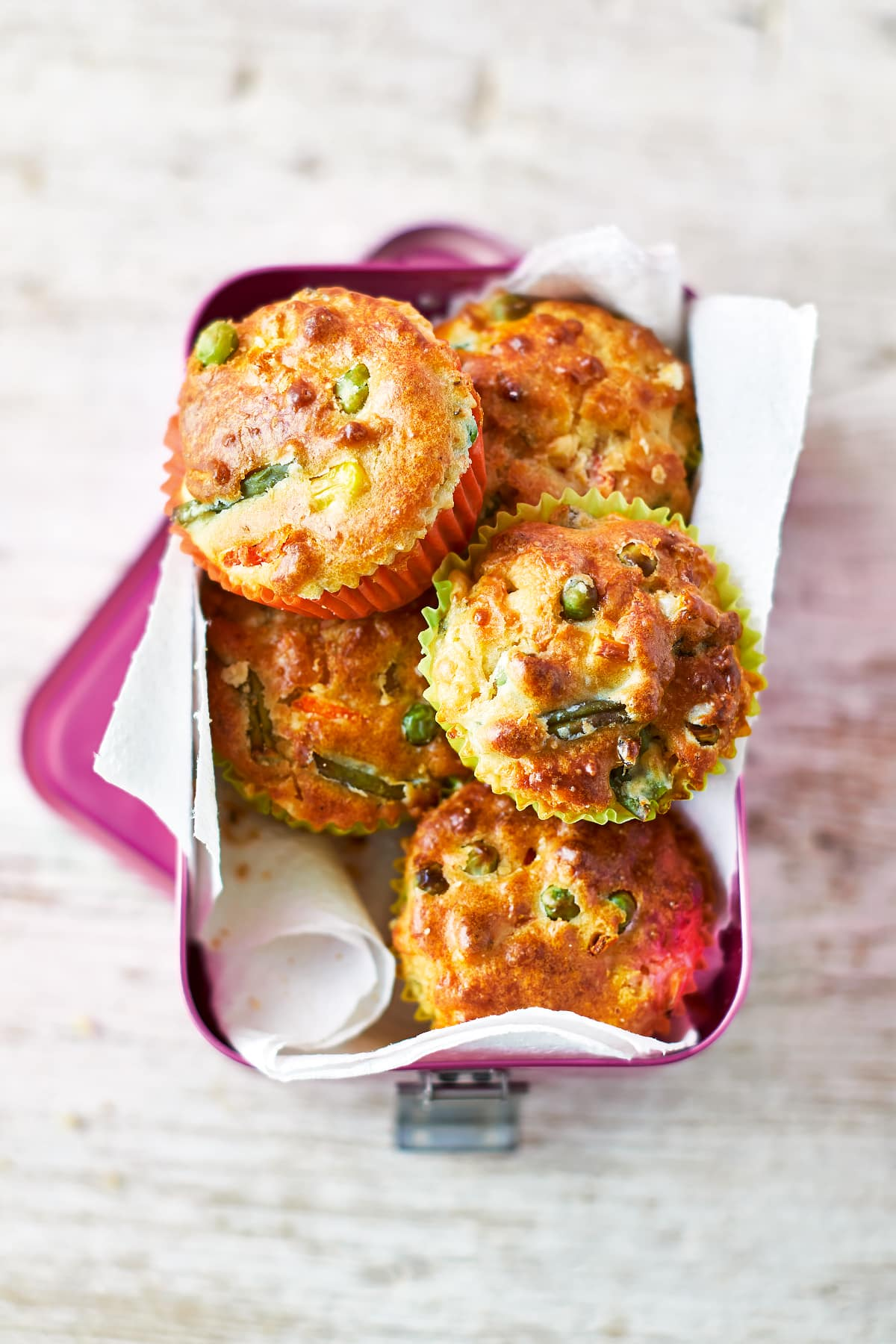 A pink lunchbox lined with paper, filled with savoury vegetable muffins. The muffins are in multicoloured cases and the tops are studded with carrots, peas, beans and sweetcorn.