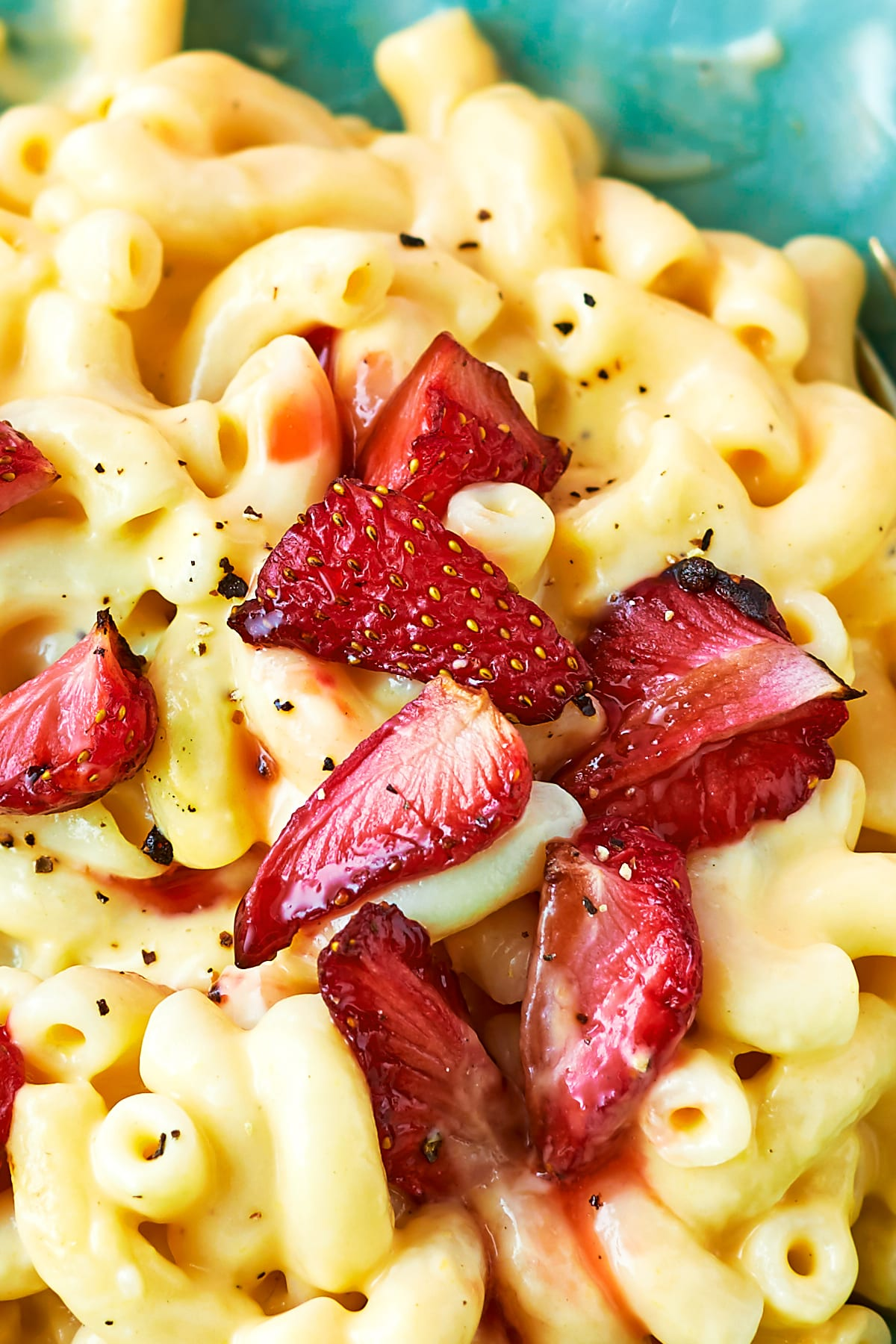 Close up of a bowl of strawberry pasta: macaroni in a cheese and butternut squash sauce, topped with roasted balsamic strawberries.