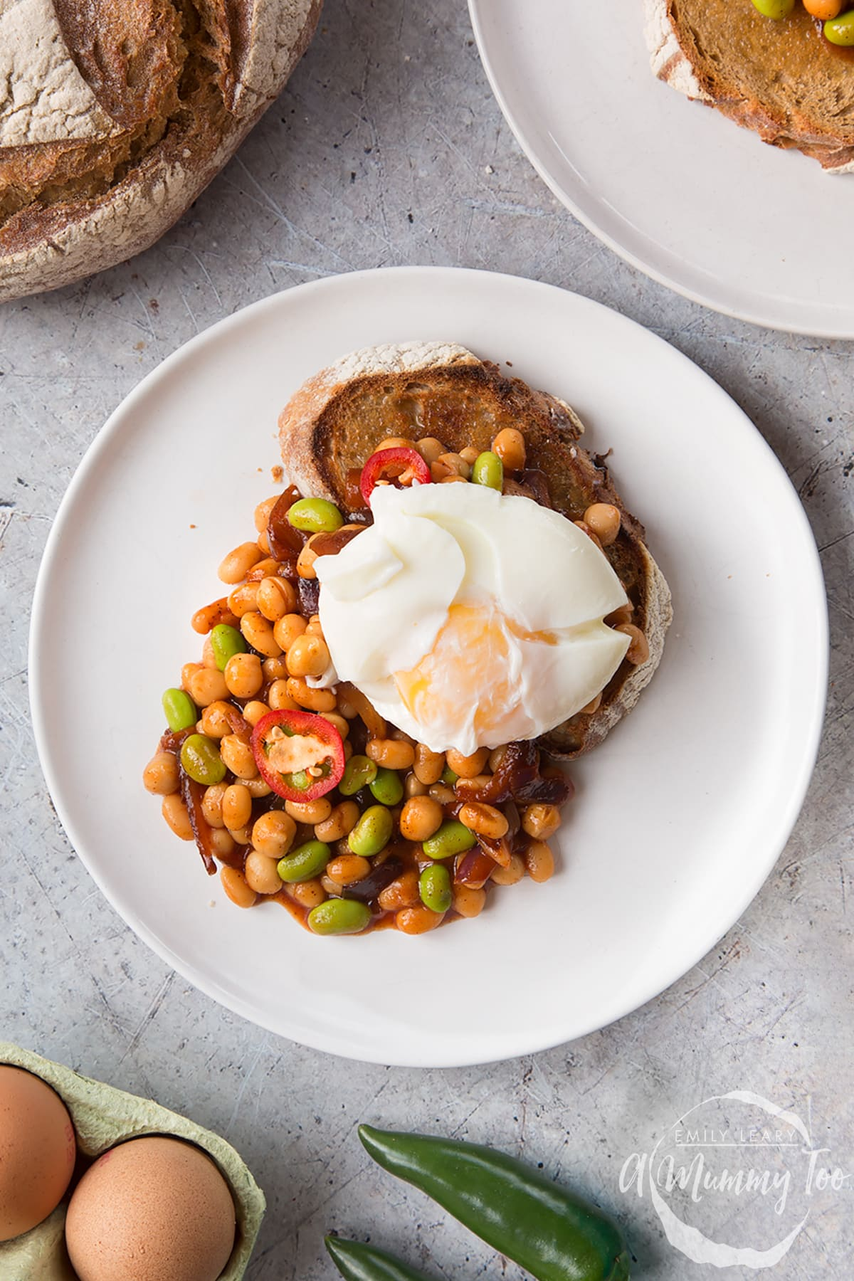 Breakfast beans with chilli, chickpeas and edamame served on sour dough toast with a poached egg on top. The yolk is not yet broken.