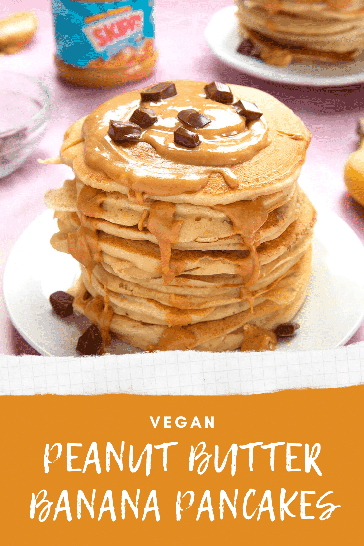 A stack of vegan peanut butter banana pancakes on a white plate. The stack is drizzled with more peanut butter and scattered with chunks of vegan chocolate. The caption reads: vegan peanut butter banana pancakes.