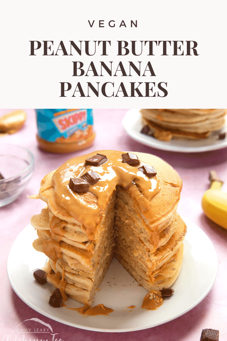 A stack of vegan peanut butter banana pancakes on a white plate. The stack is drizzled with more peanut butter and scattered with chunks of vegan chocolate. A wedge of pancakes is cut from the whole stack. The caption reads: vegan peanut butter banana pancakes.