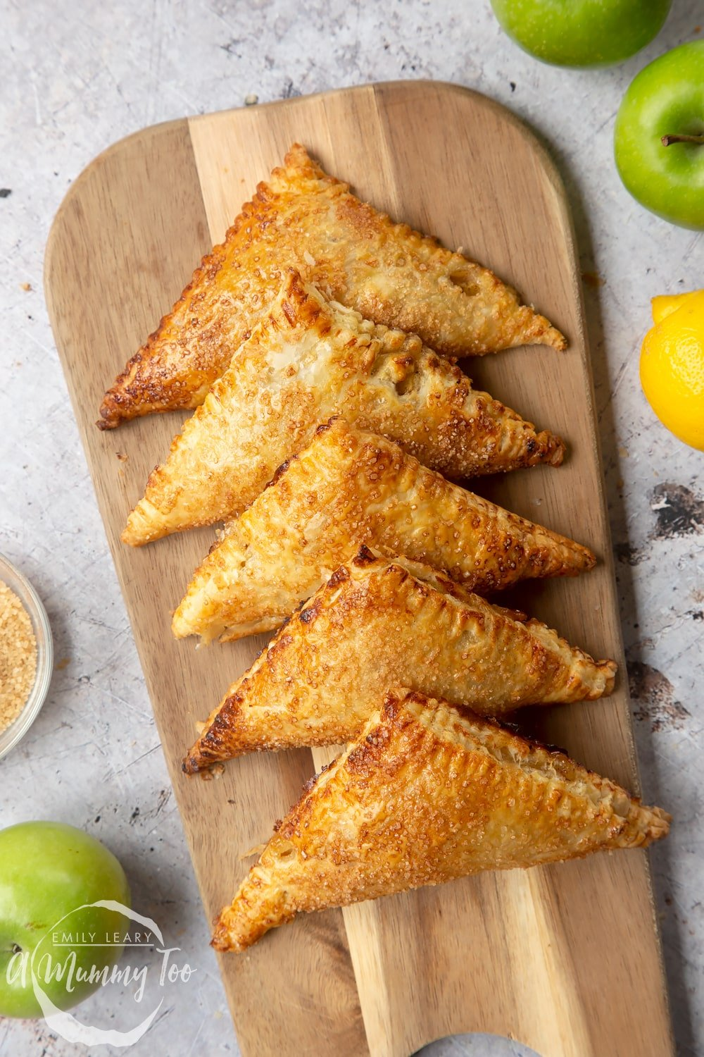 Overhead shot of an Apple cinnamon turnovers served on a wooden plate with a mummy too logo in the lower-left corner