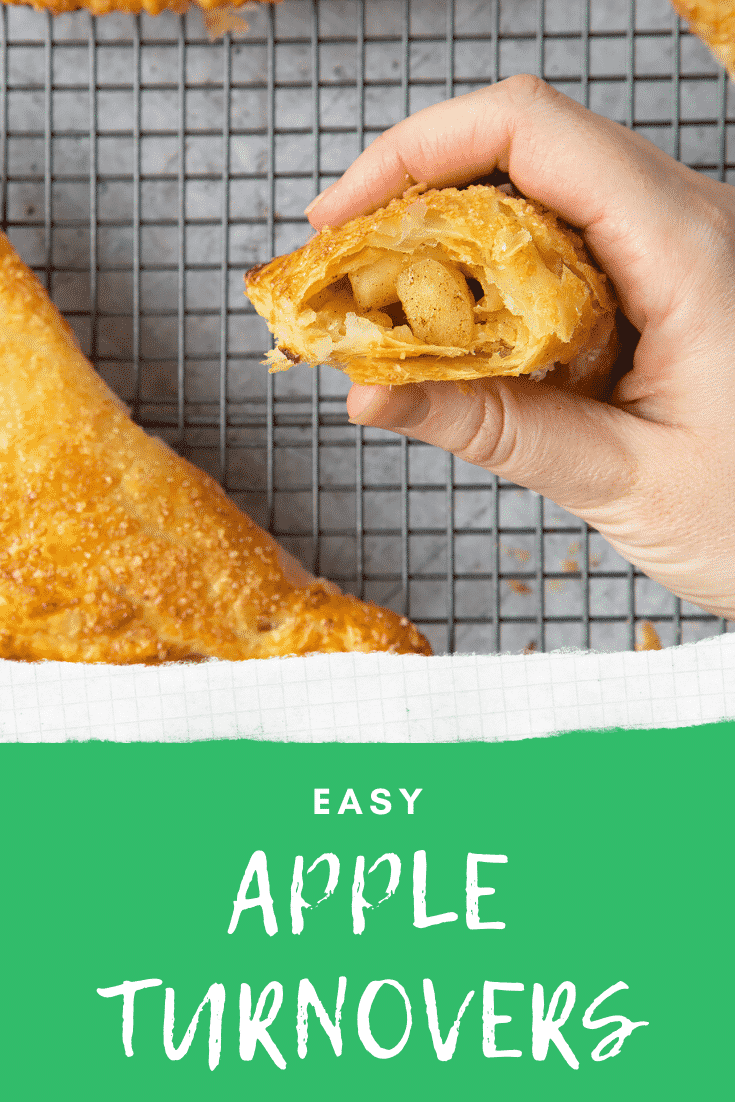 Overhead shot of inside of an apple turnover with a hand holding it. At the bottom of the image there's some text describing the image for pinterest.