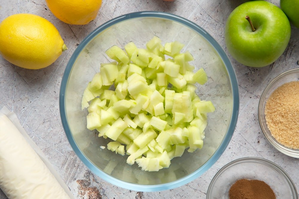 Overhead shot of chopped apples in a clear bowl