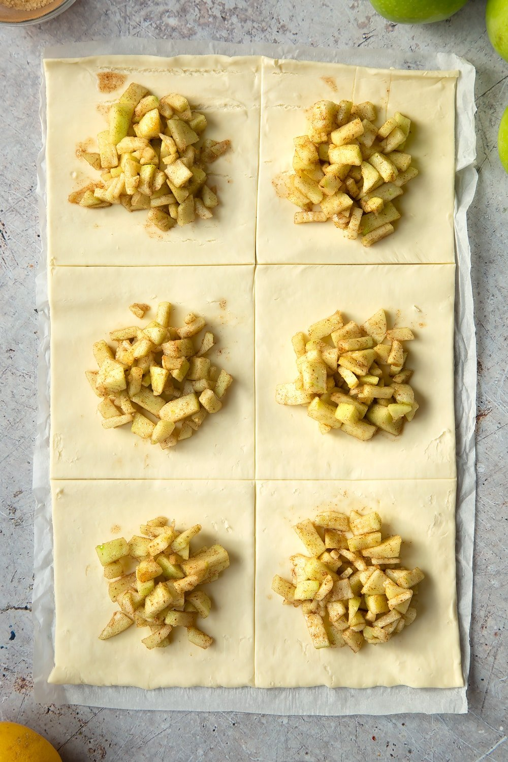 Overhead shot of one sheet of puff pastry with six divisions with apple filling on top