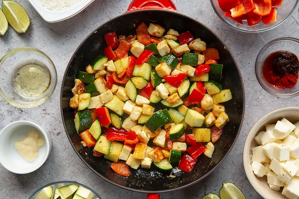 Overhead shot of courgette, red pepper, and halloumi in a large red pan