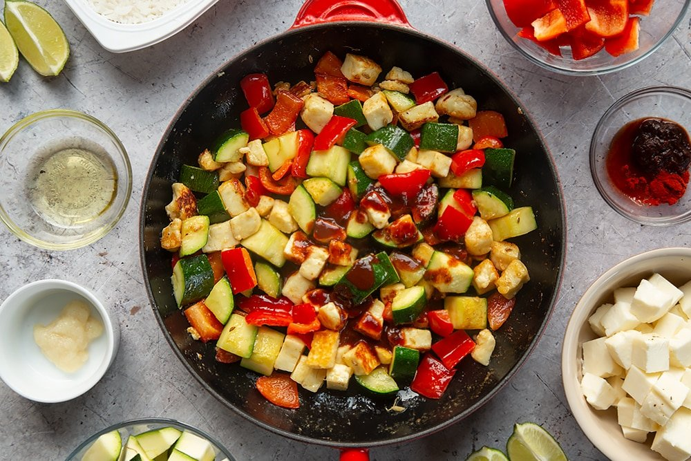 Overhead shot of courgette, red pepper, and halloumi in a large red pan topped with sauce