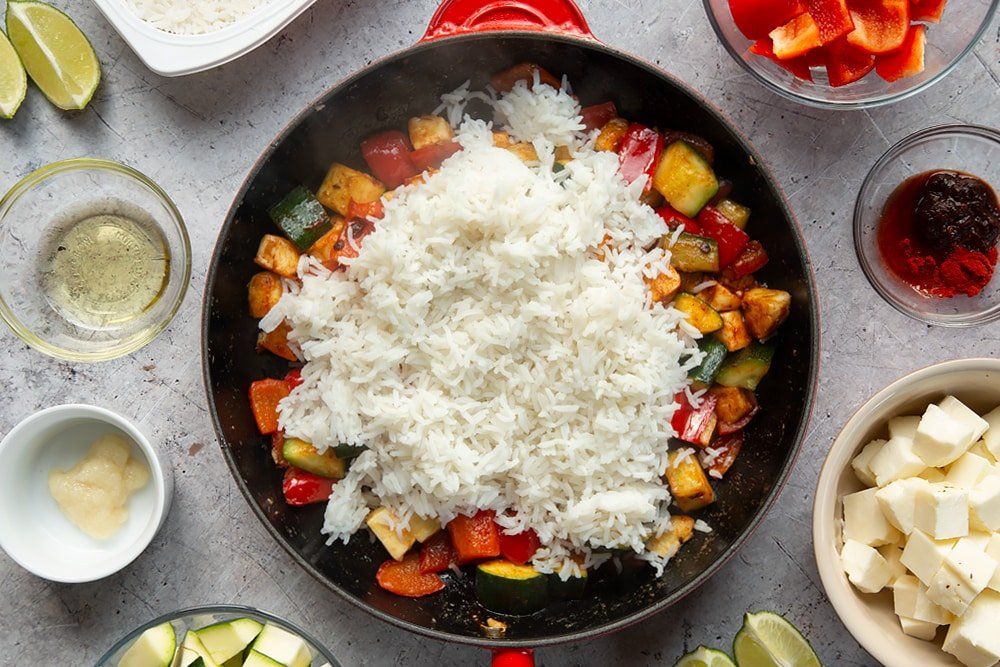 Overhead shot of fried vegetables topped with rice in a large pan