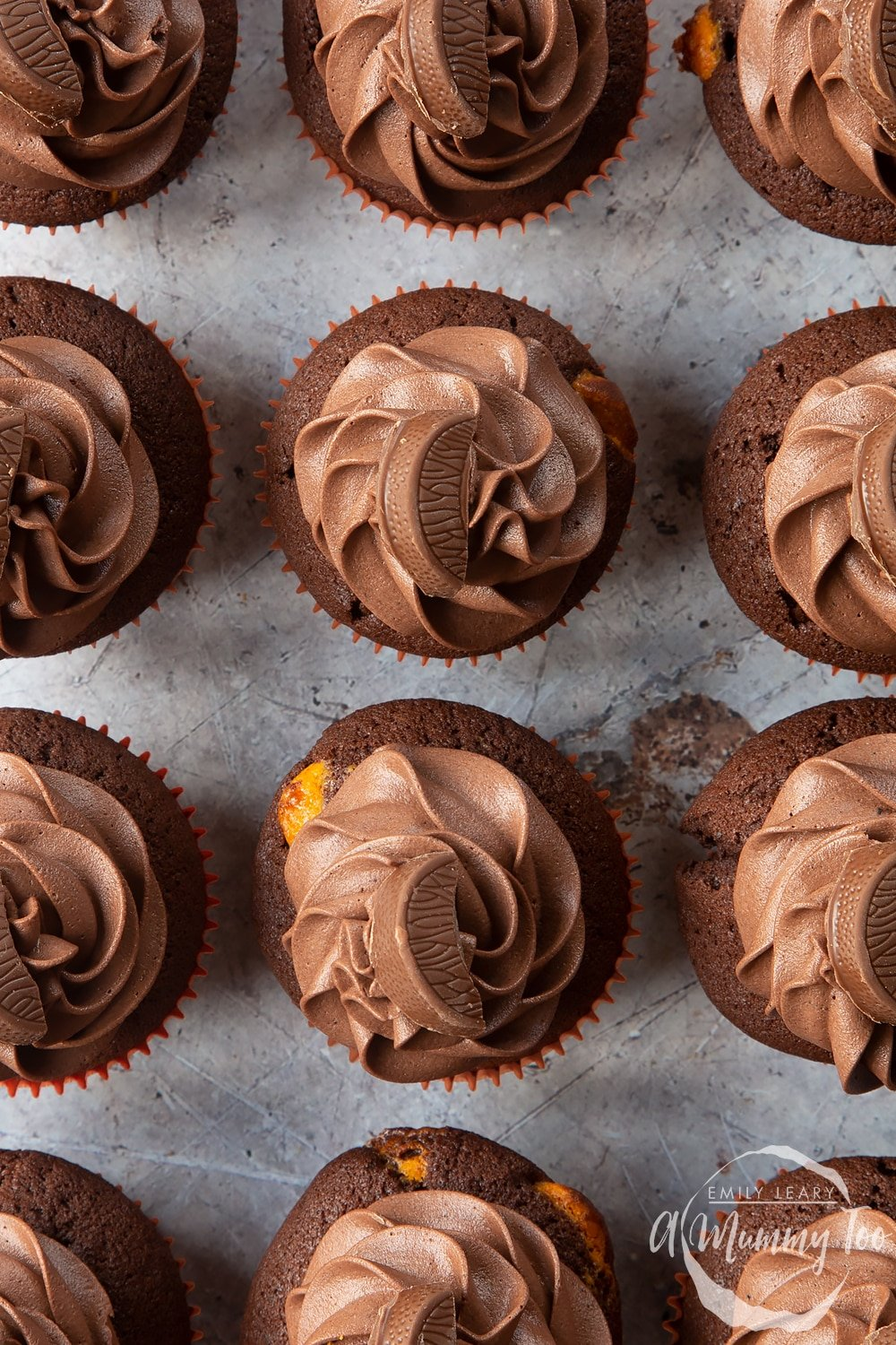 Overhead shot of chocolate orange muffins topped with Chocolate Orange bar and chocolate frosting with a mummy too logo in the lower-right corner
