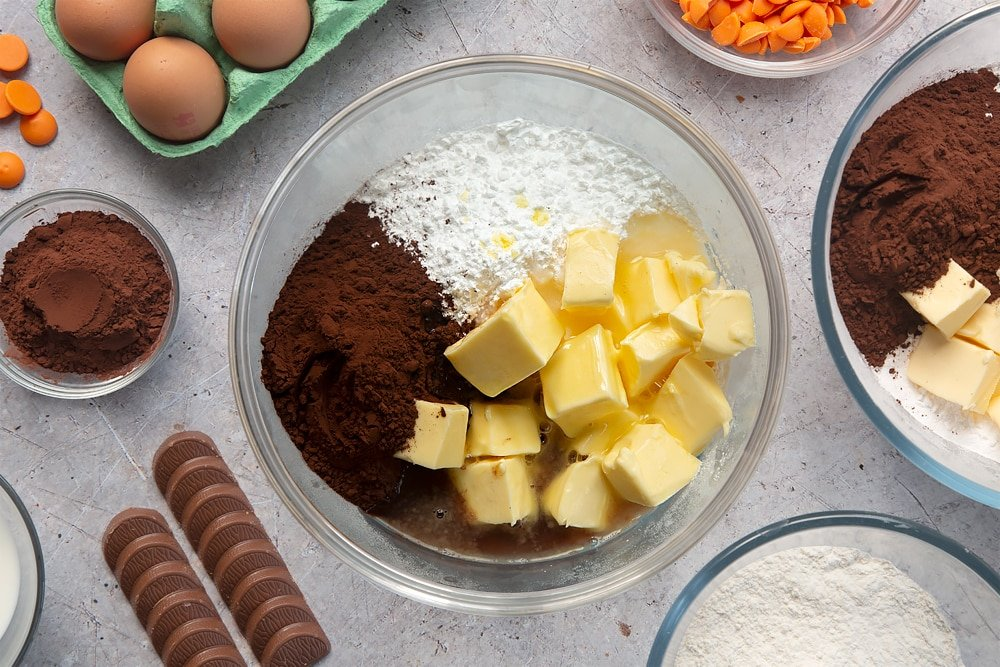 Overhead shot of butter, icing sugar, cocoa powder, hot water and orange essence in a large mixing bowl