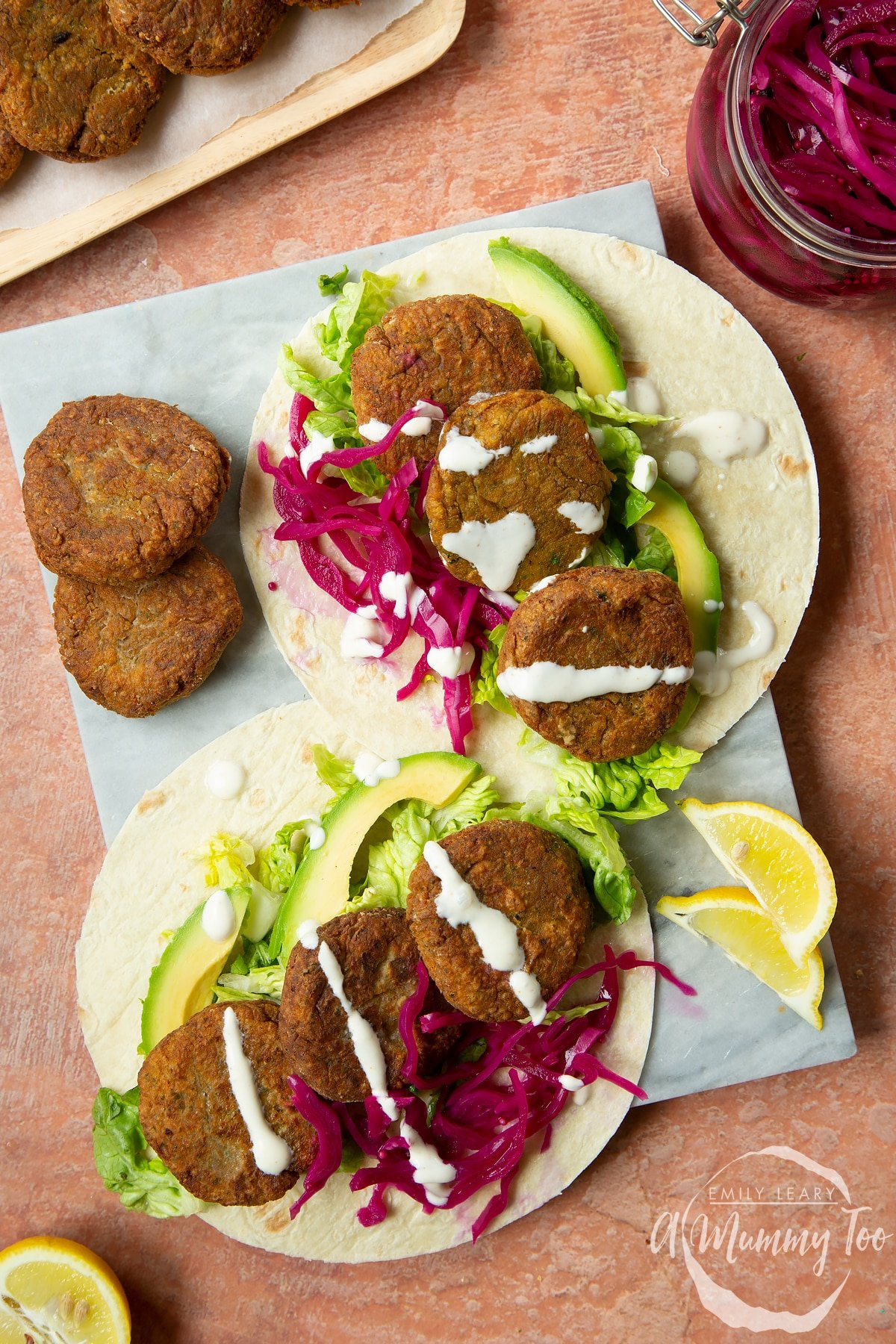 Two harissa falafel wraps arranged on a board with pickled cabbage and salad. Drizzled with tahini dressing.
