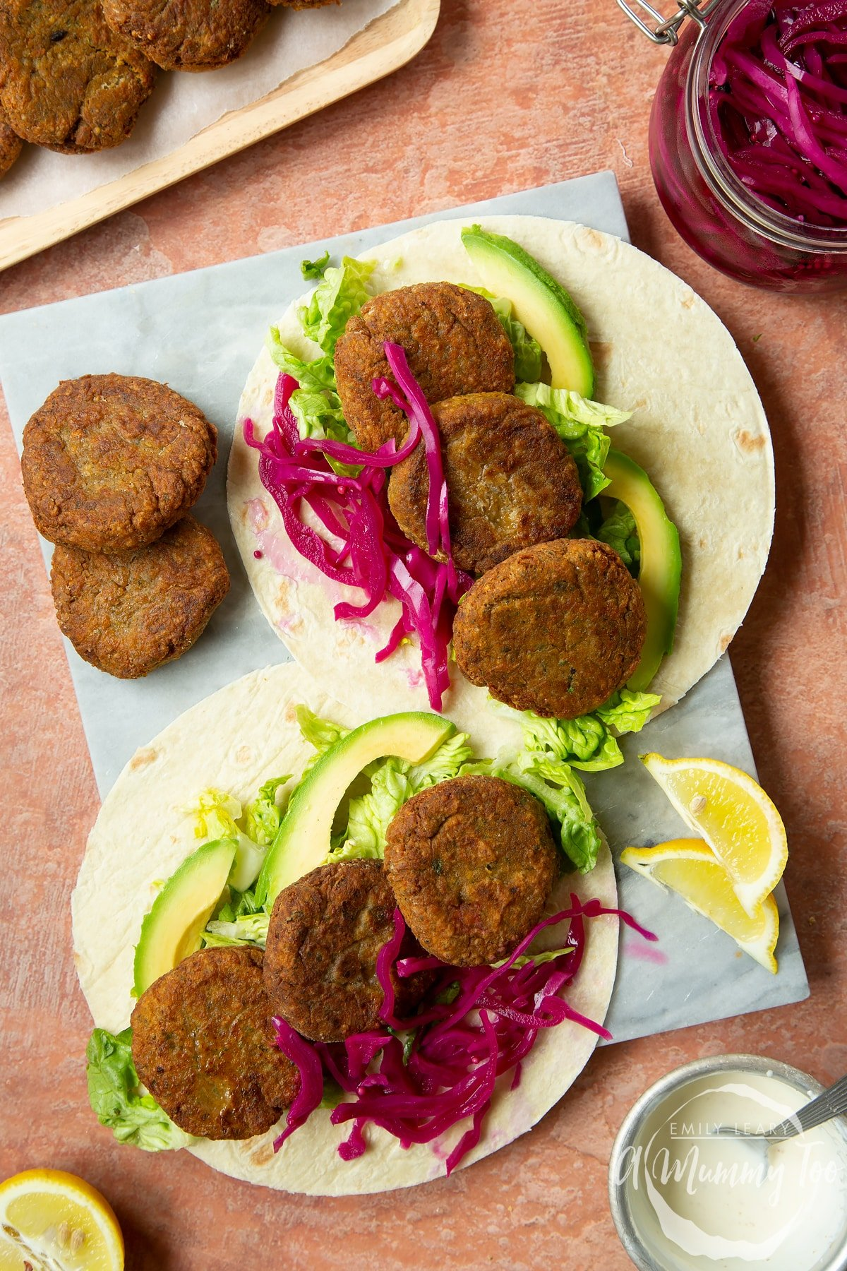 Two harissa falafel wraps arranged on a board with pickled cabbage and salad.