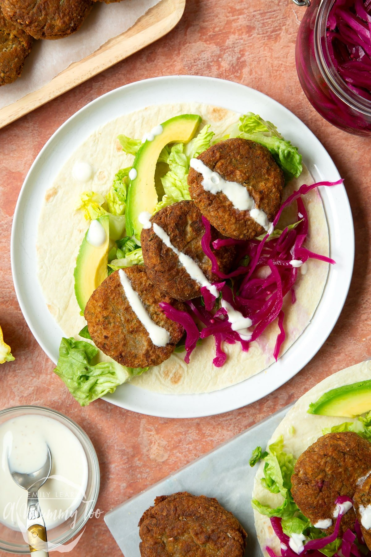 A harissa falafel wrap arranged on a plate with pickled cabbage and salad, drizzled with tahini dressing.