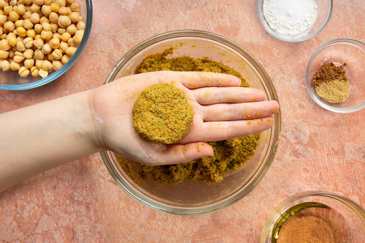 A hand holds a harissa falafel patty over a bowl of harissa falafel mix.