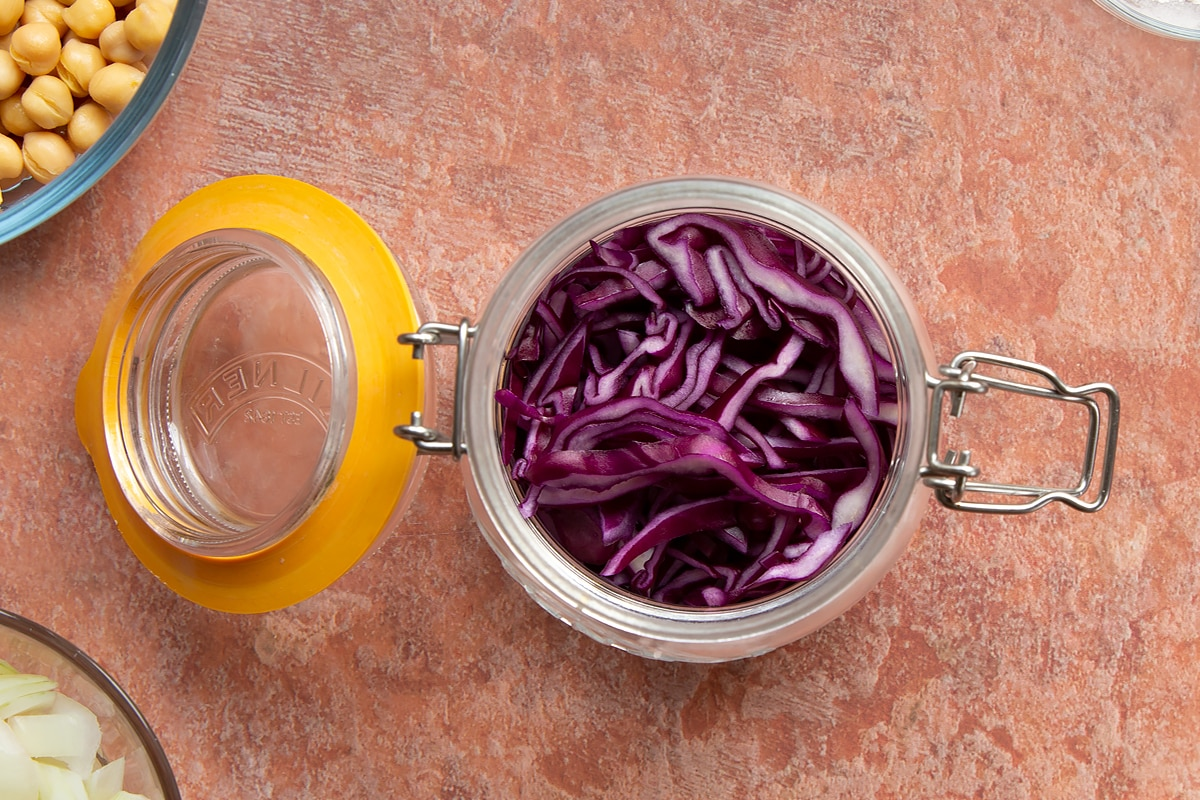 A preserving jar containing thinly sliced shallots and red cabbage.