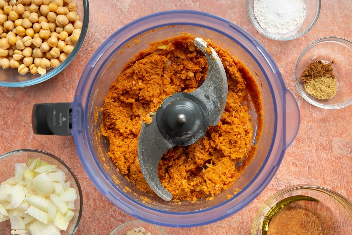 A food processor containing a harissa falafel paste made from chickpeas, spices, garlic, flour, baking powder and chopped onion.