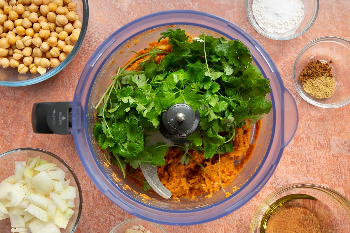 A food processor containing a harissa falafel paste made from chickpeas, spices, garlic, flour, baking powder and chopped onion. Topped with fresh parsley and coriander.