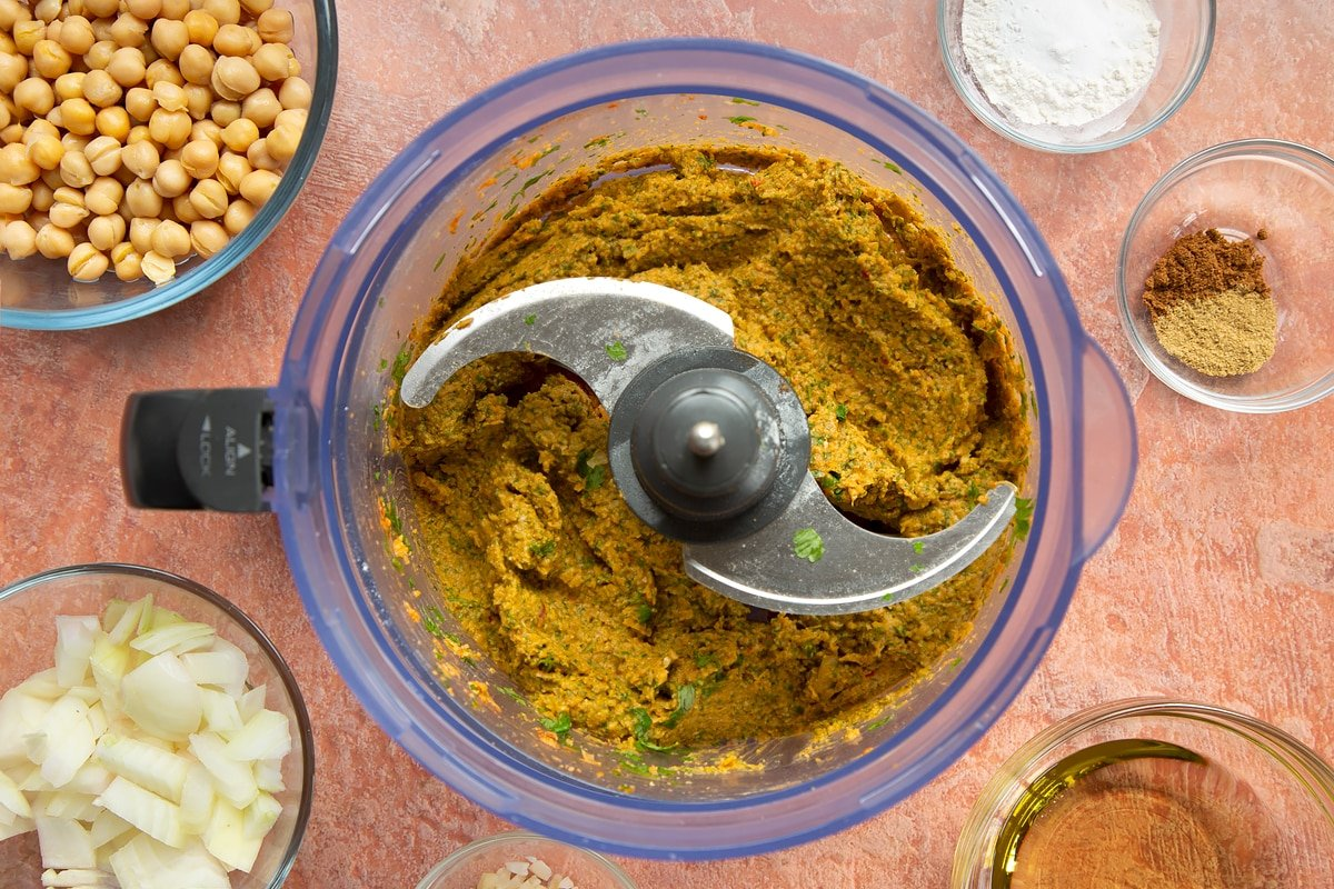 A food processor containing a harissa falafel paste made from chickpeas, spices, garlic, flour, baking powder, chopped onion, fresh parsley and coriander.