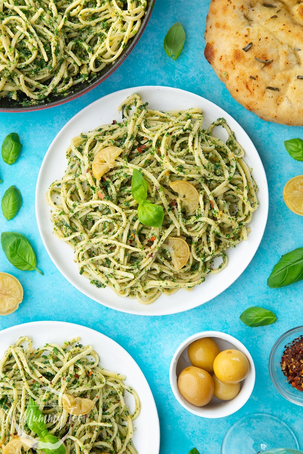 Two white plates with kale pesto linguine, topped with basil and slices of preserved lemons.