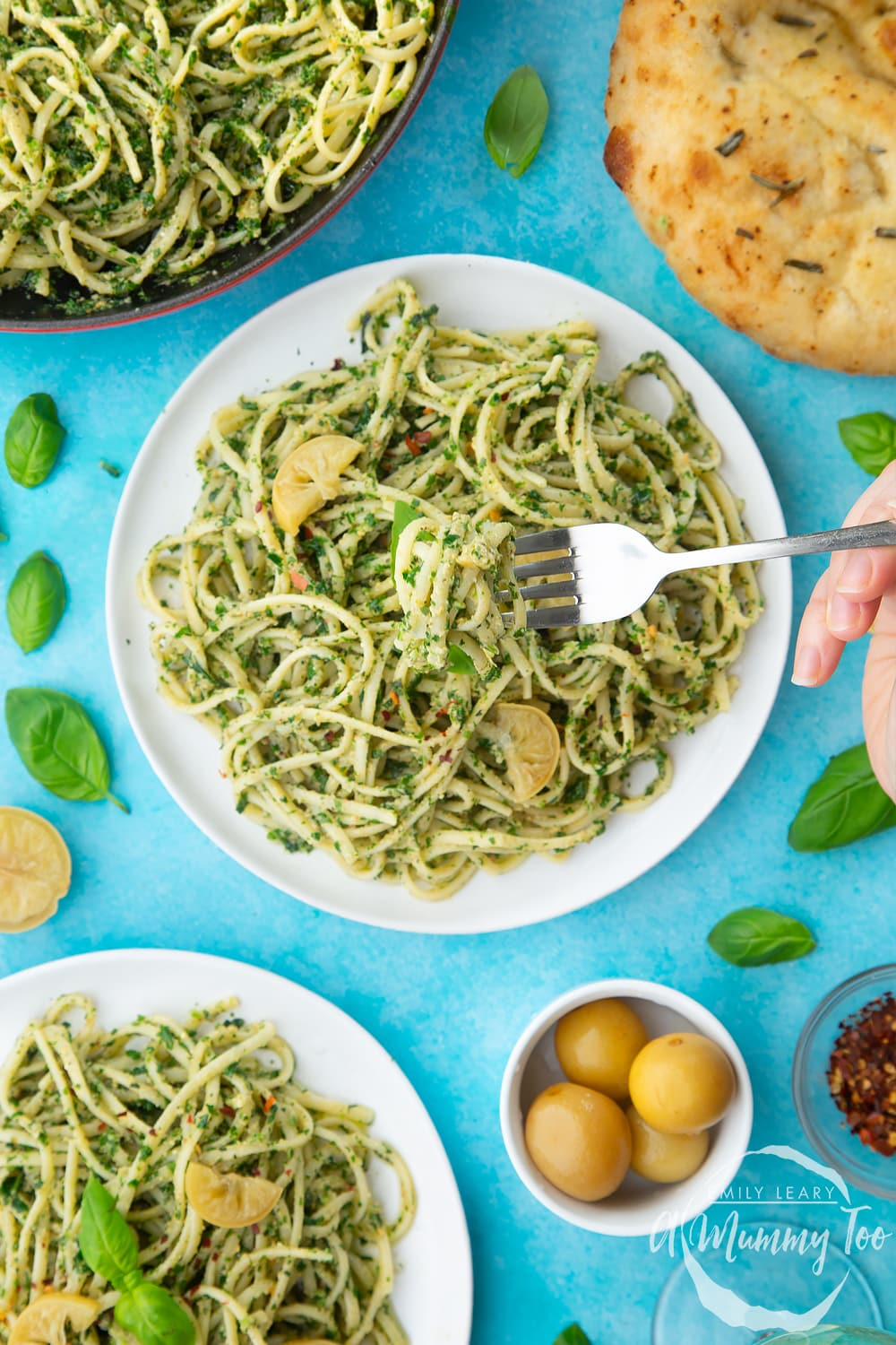 Two white plates with kale pesto linguine, topped with basil and slices of preserved lemons. A fork is lift pasta from the main plate.