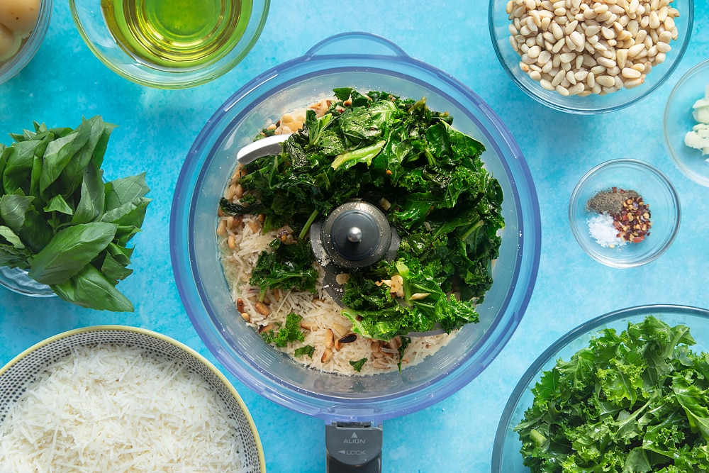 A food processor with olive oil, grated parmesan, toasted pine nuts, wilted kale and basil. The food processor bowl is surrounded by ingredients for kale pesto linguine.