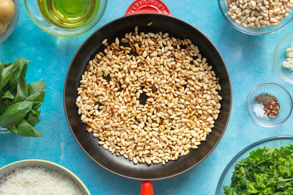 A pan containing toasted pine nuts. The pan is surrounded by ingredients for kale pesto linguine.