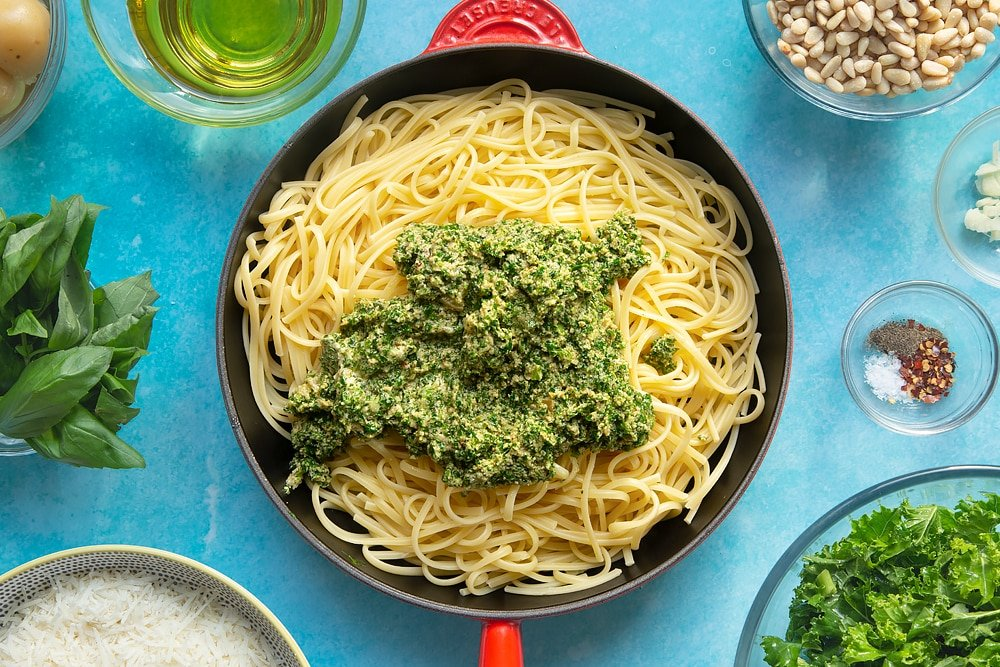 A pan of freshly cooked linguine topped with kale pesto. The bowl is surrounded by ingredients for kale pesto linguine.