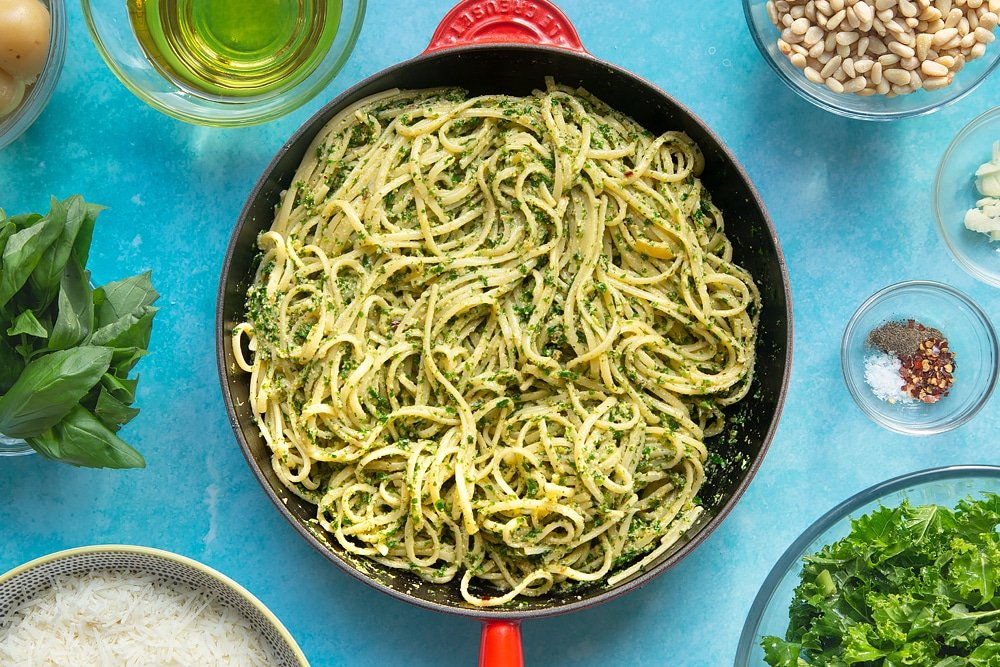 A pan of freshly cooked kale pesto linguine. The bowl is surrounded by ingredients for kale pesto linguine.