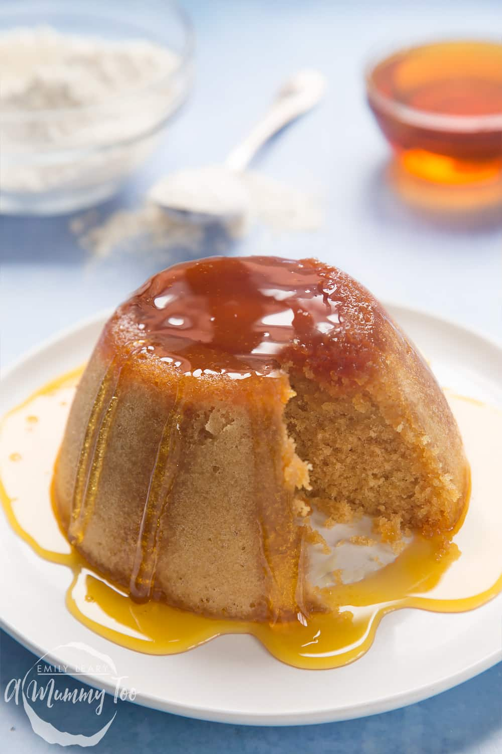 Front angle shot of syrup sponge pudding served in a white plate with honey with a mummy too logo in the lower-left corner