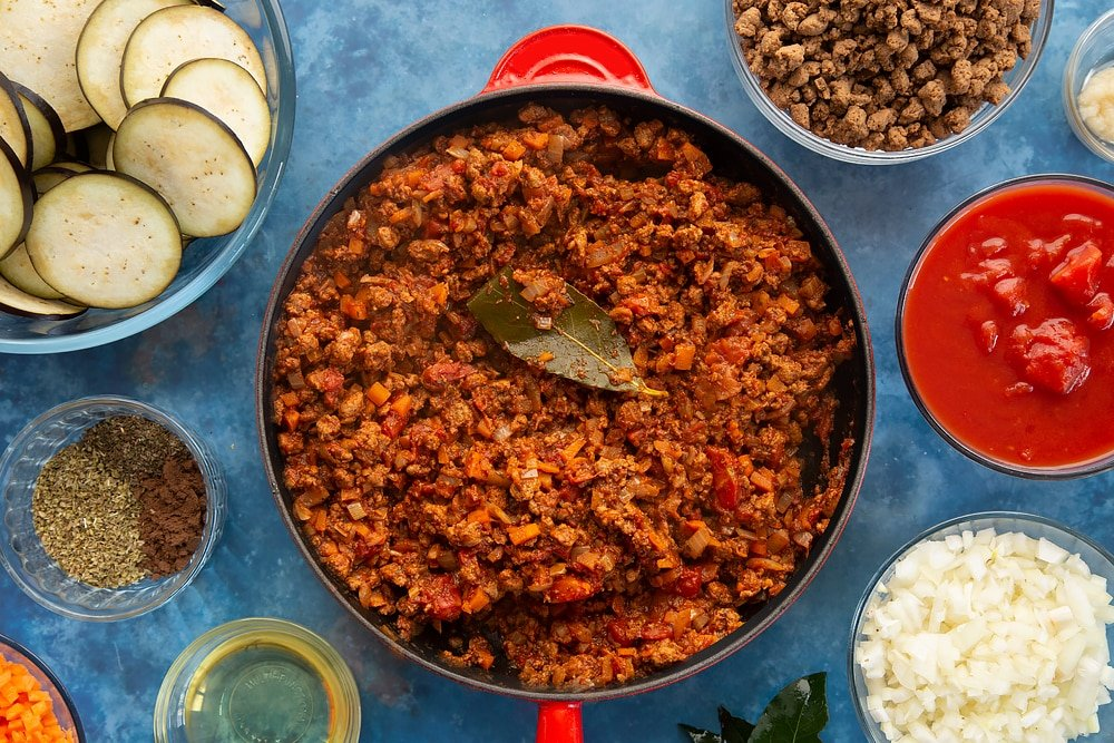 Overhead shot of Quorn Meat Free Mince topped with bayleaf on a red saucepan surrounded by aubergine minced meat spices onion oil carrot garlic bayleaves and chopped tomatoes