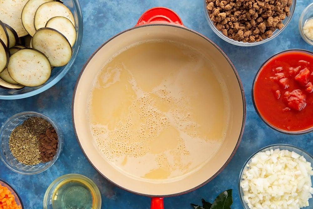 Overhead shot of butter, milk mixture, and flour in a red saucepan