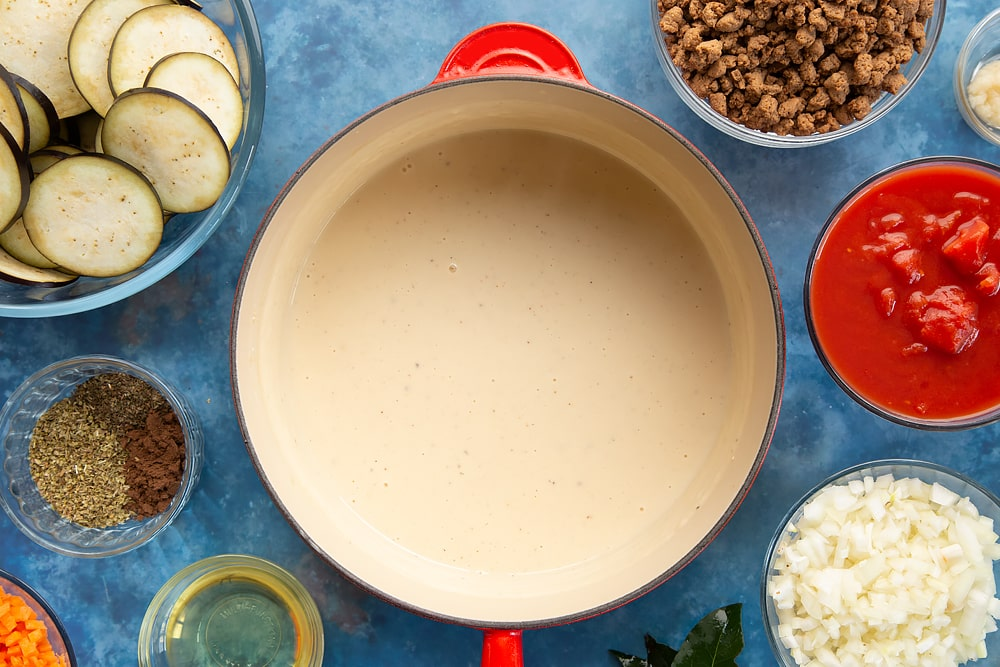 Overhead shot of white sauce in a red saucepan surrounded by aubergine minced meat spices onion oil carrot garlic bayleaves and chopped tomatoes
