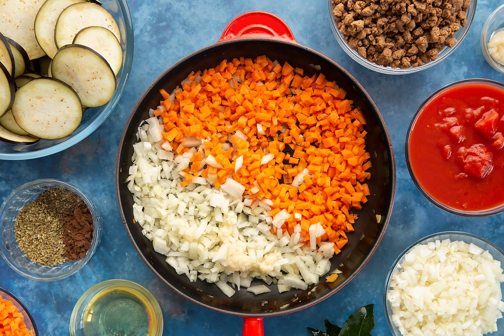 Overhead shot of carrots onion and garlic on a red saucepan surrounded by aubergine minced meat spices onion oil carrot garlic bayleaves and chopped tomatoes