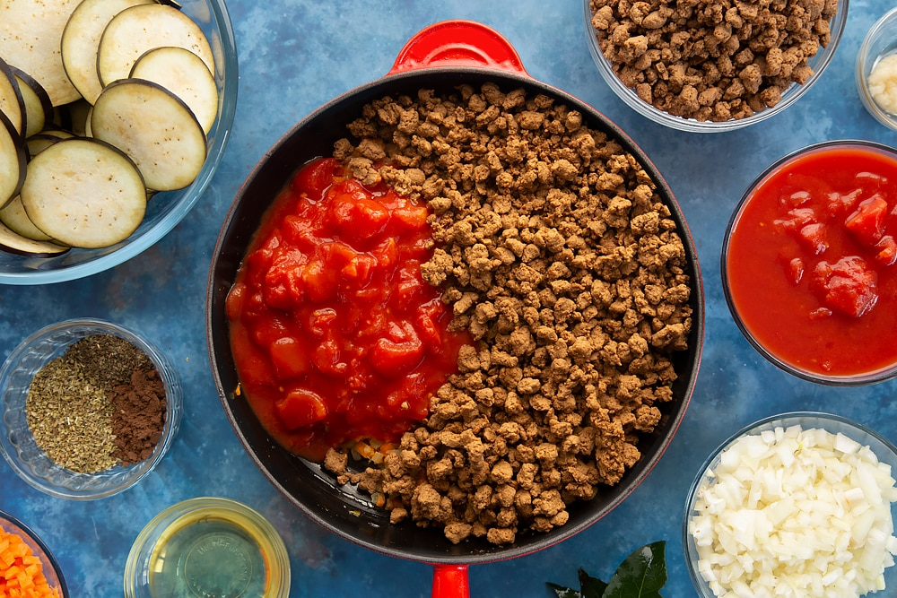 Overhead shot of Quorn Meat Free Mince and tomatoes on a red saucepan surrounded by aubergine minced meat spices onion oil carrot garlic bayleaves and chopped tomatoes