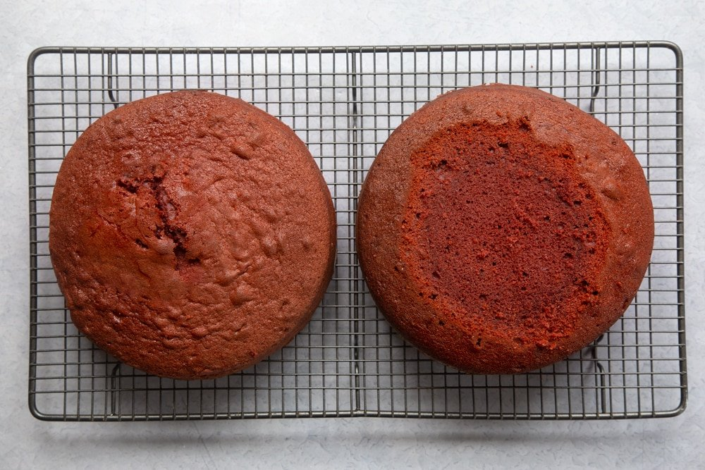 Two cooked red velvet sponges on. a cooling rack. One has had its top trimmed to create a flat surface.