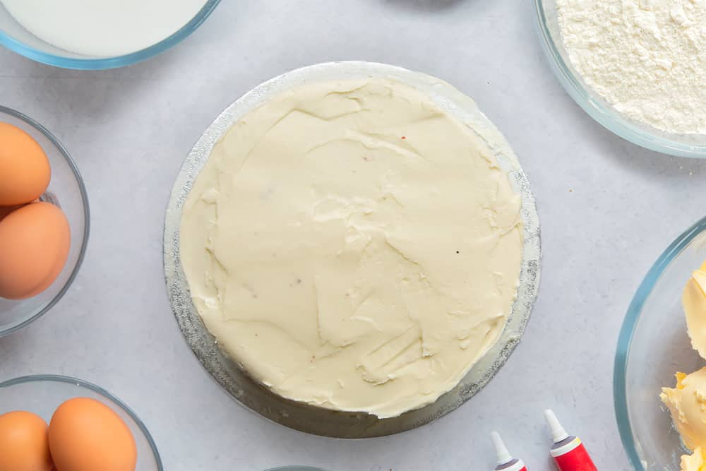 A silver cake board with a red velvet cake on it, covered with cream cheese frosting. Ingredients to make filled red velvet cake surround the board.