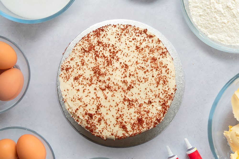 A silver cake board with a red velvet cake on it, covered with cream cheese frosting and sprinkled with cake crumbs. Ingredients to make filled red velvet cake surround the board.