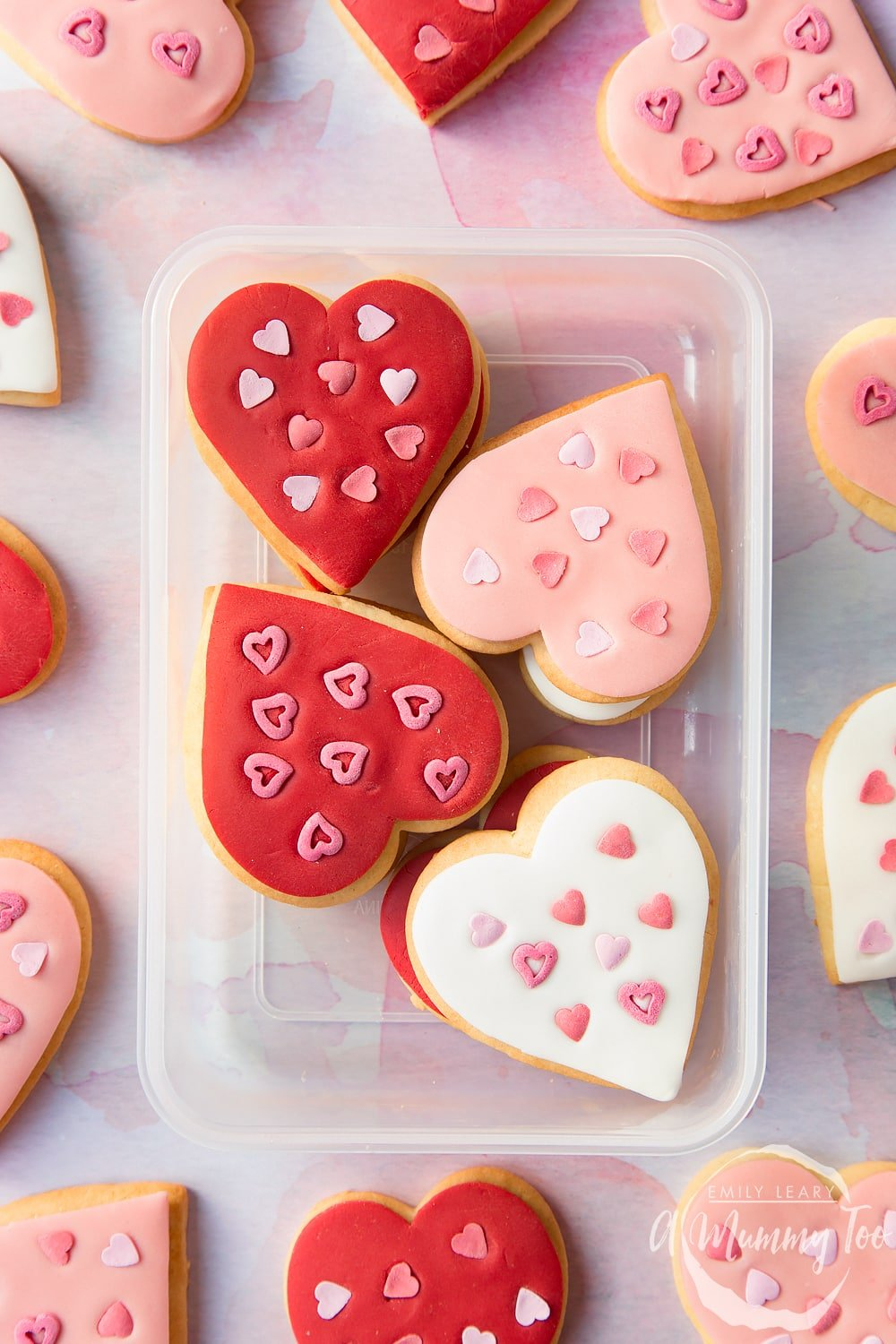 Overhead shot of valentines day cookies stacked in a clear plastic container with A Mummy Too logo in the bottom right hand corner