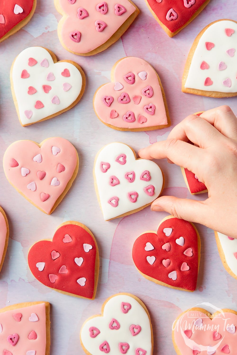Overhead shot of a hand holding a Heart biscuit with a mummy too logo in the lower-right corner