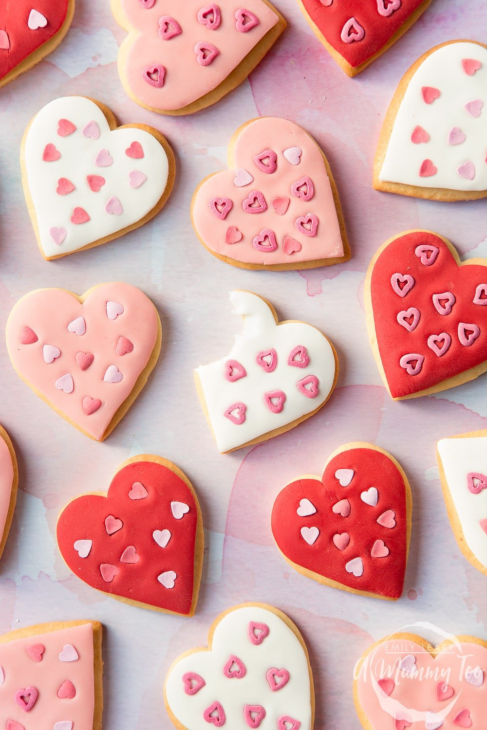 Overhead shot of heart shaped cookies for Valentines day with one cookie with a bite missing in the centre with A Mummy Too logo in the bottom right hand corner