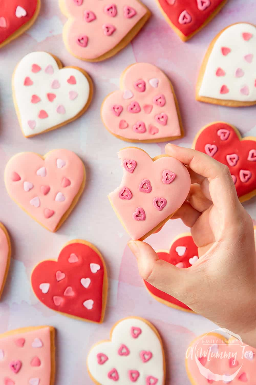Overhead shot of a hand holding a Heart biscuit for Valentine's Day with a mummy too logo in the lower-right corner