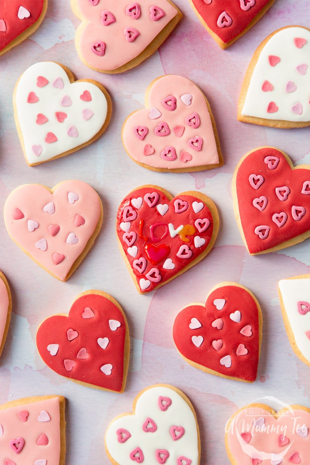 Overhead shot of Valentines day cookies with additional icing writing with the A Mummy Too logo in the bottom right hand corner