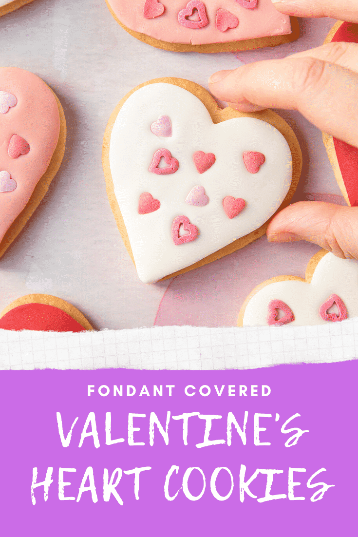 graphic text FONDANT COVERED VALENTINE'S DAY COOKIES above an Overhead shot of a hand holding a valentines day cookies