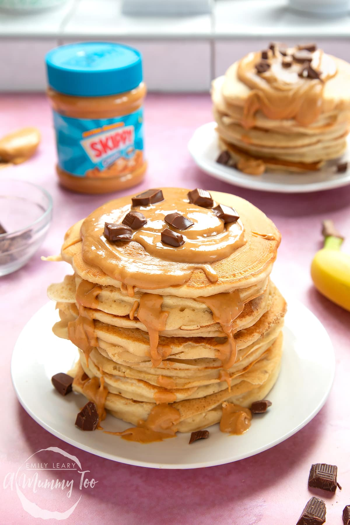 A stack of vegan peanut butter banana pancakes on a white plate. The stack is drizzled with more peanut butter and scattered with chunks of vegan chocolate.