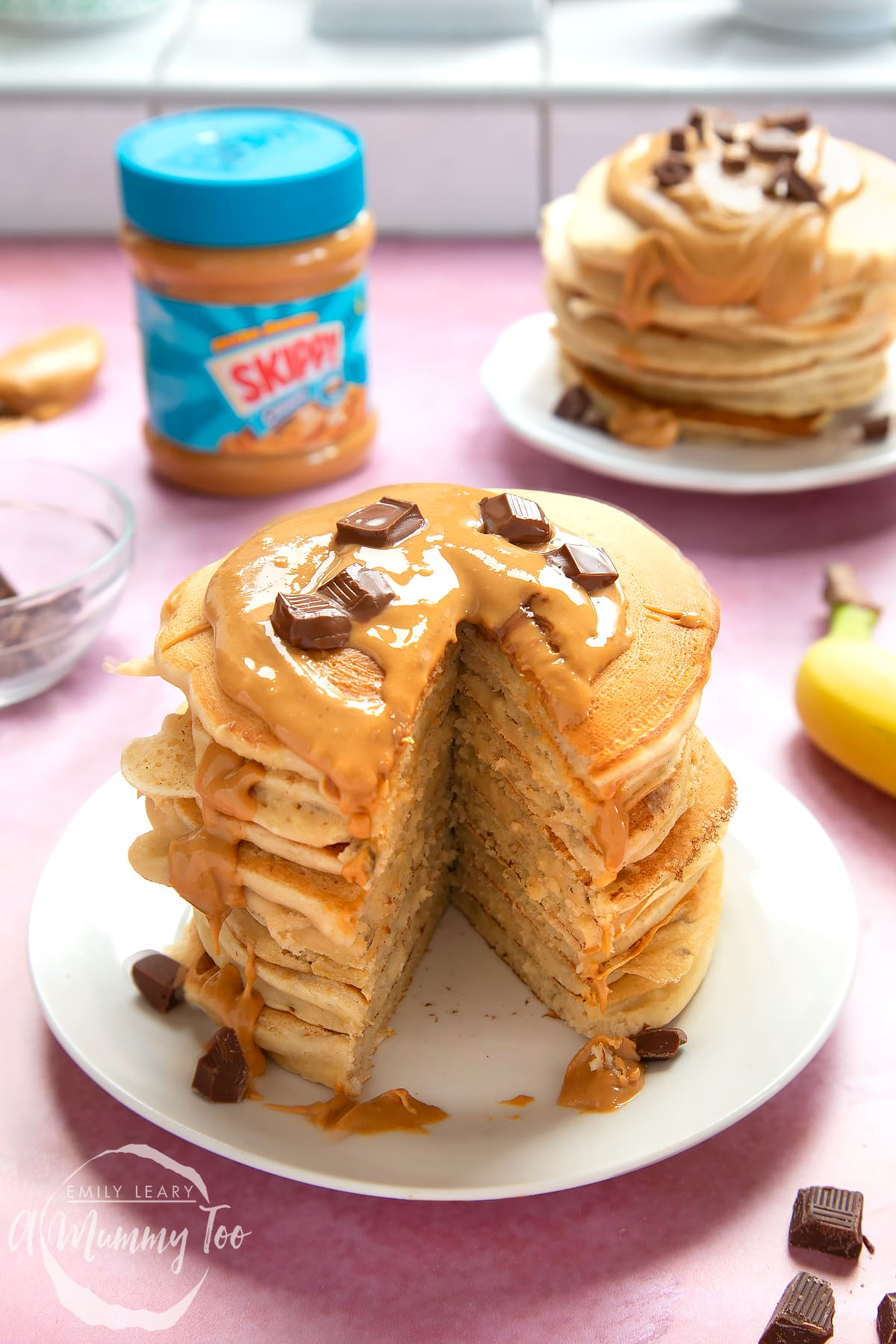 A stack of vegan peanut butter banana pancakes on a white plate. The stack is drizzled with more peanut butter and scattered with chunks of vegan chocolate. A large slice has been taken out of the whole stack, revealing the fluffy inner.