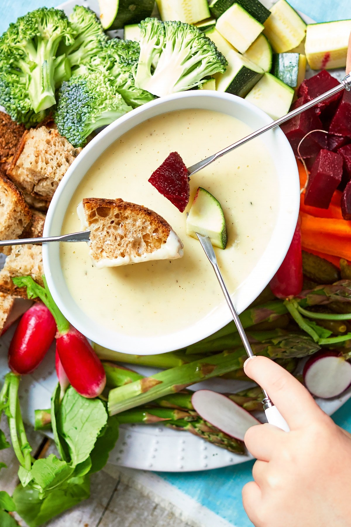 An overhead view of a vegetable fondue platter. A family of hands reach in with fondue forks to dip bread, beetroot, courgette into cheese sauce.