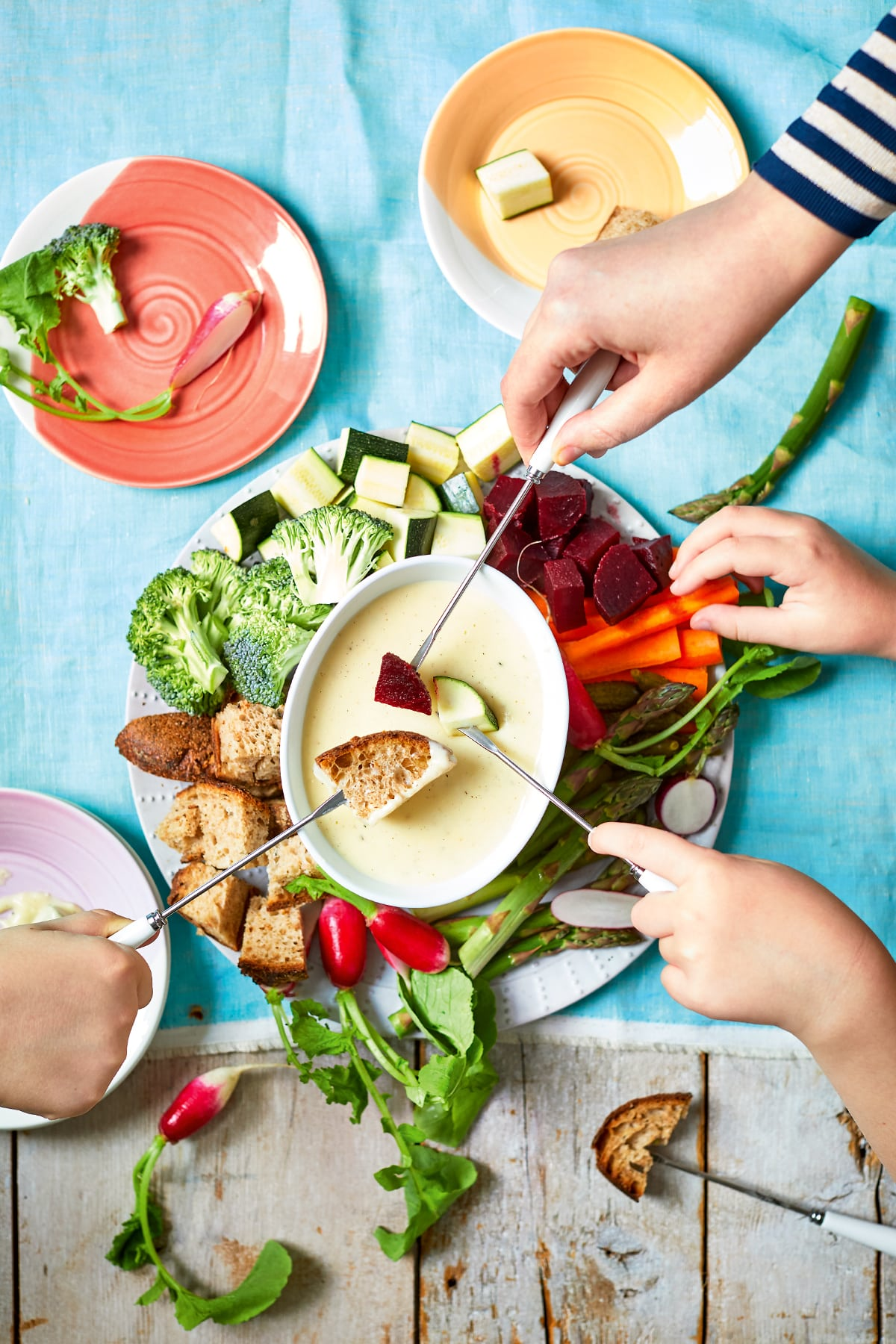 An overhead view of a vegetable fondue platter. A family of hands reaches in with fondue forks to dip bread, beetroot, courgette and more into the cheese sauce.
