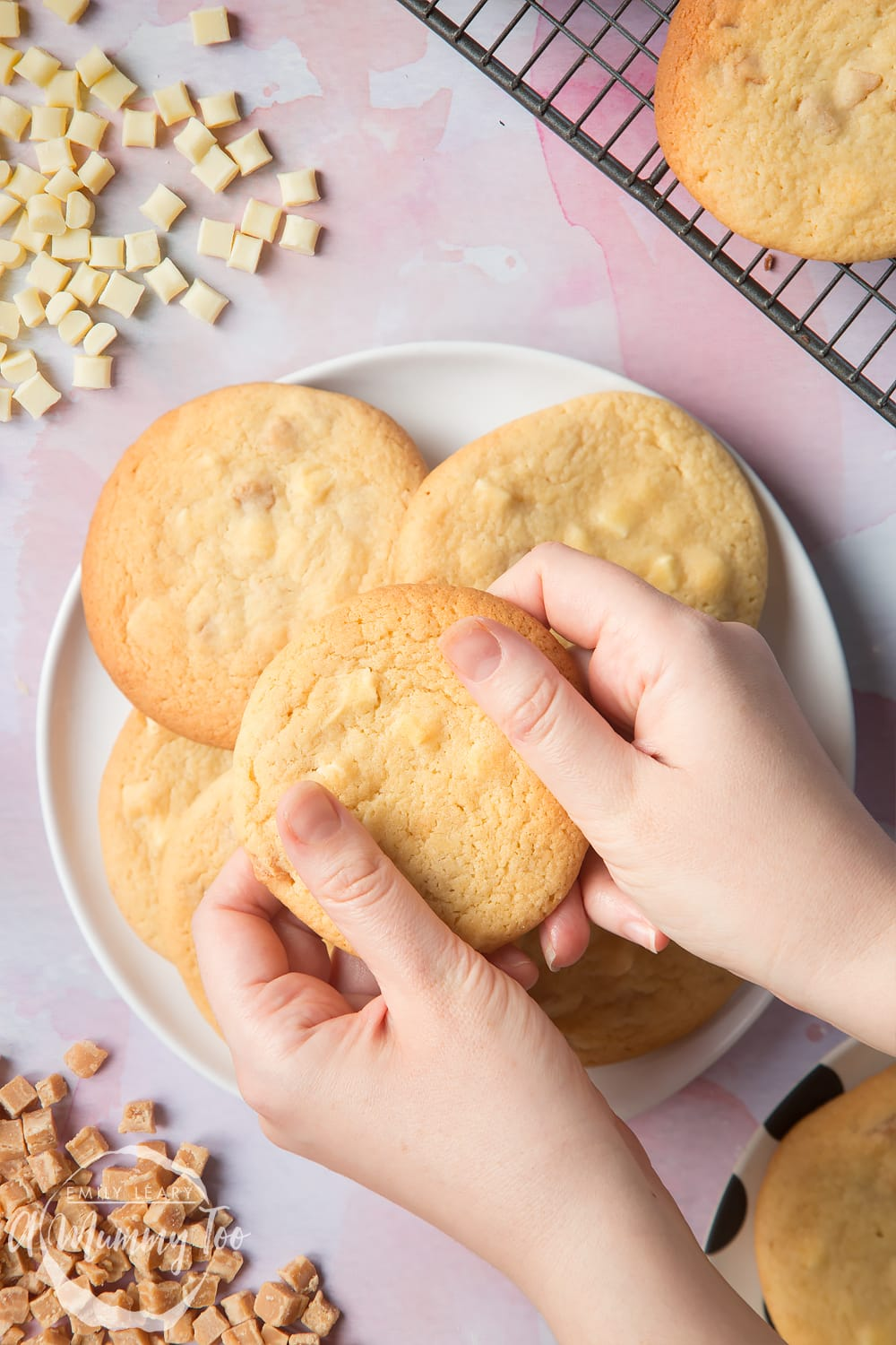 Overhead shot of a hands holding a Fudge and white chocolate chip cookie open with a mummy too logo in the lower-left corner